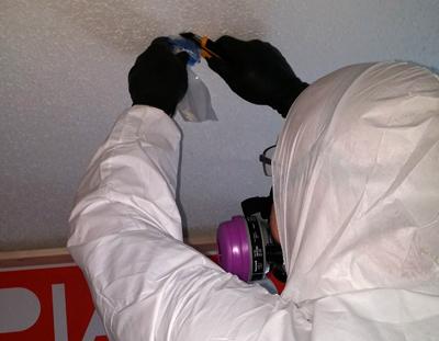 technician collecting an asbestos sample
