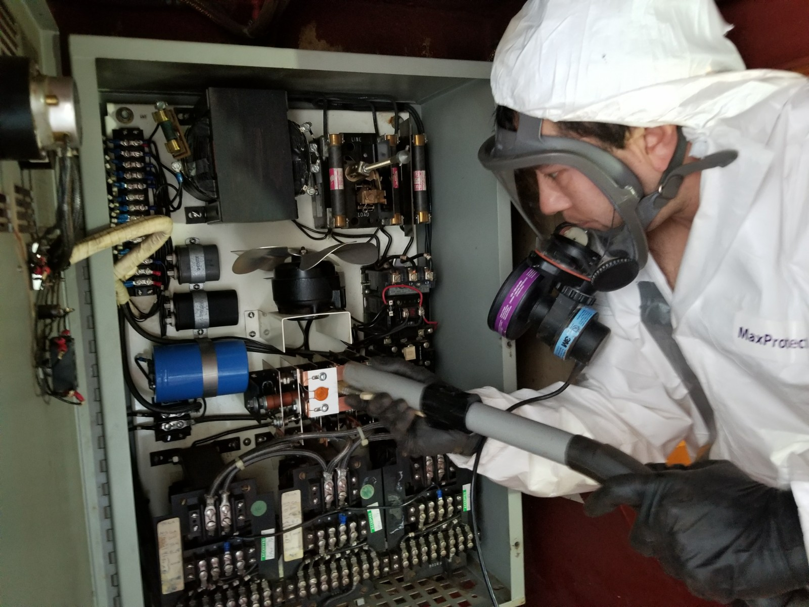 technician cleaning electronics panel